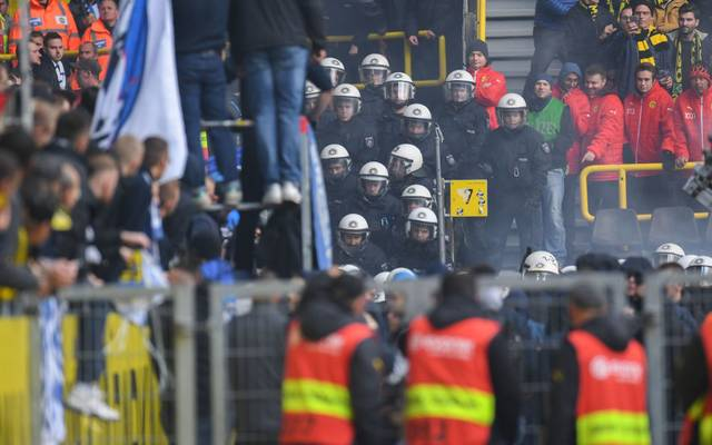 Policemen keep a close eye on Berlin fans who lite flares during the German first division Bundesliga football match BVB Borussia Dortmund v Hertha Berlin in Dortmund, western Germany, on October 27, 2018. (Photo by Patrik STOLLARZ / AFP) / RESTRICTIONS: DFL REGULATIONS PROHIBIT ANY USE OF PHOTOGRAPHS AS IMAGE SEQUENCES AND/OR QUASI-VIDEO        (Photo credit should read PATRIK STOLLARZ/AFP/Getty Images)