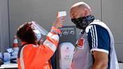 SINSHEIM, GERMANY - MAY 16: A member of the Red Cross measures the temperature of photographer Torsten Wagner at the entrance of the stadium prior to the Bundesliga match between TSG 1899 Hoffenheim and Hertha BSC at PreZero-Arena on May 16, 2020 in Sinsheim, Germany. The Bundesliga and Second Bundesliga is the first professional league to resume the season after the nationwide lockdown due to the ongoing Coronavirus (COVID-19) pandemic. All matches until the end of the season will be played behind closed doors. (Photo by Thomas Kienzle/Pool via Getty Images)