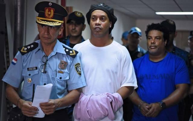 Ronaldinho (M.) und sein Bruder Roberto Assis (r.) werden in Handschellen durch das Gerichtsgebäude von Asuncion geleitet