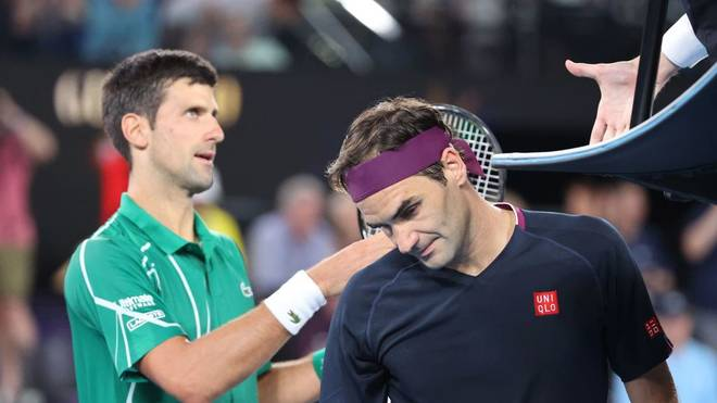 Serbia's Novak Djokovic (L) prepares to shake hands with the umpire as Switzerland's Roger Federer walks off the court after their men's singles semi-final match on day eleven of the Australian Open tennis tournament in Melbourne on January 30, 2020. (Photo by DAVID GRAY / AFP) / IMAGE RESTRICTED TO EDITORIAL USE - STRICTLY NO COMMERCIAL USE (Photo by DAVID GRAY/AFP via Getty Images)