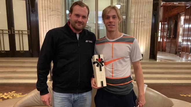 YONEX-Manager Carsten Neuhaus (l.) überreicht Denis Shapovalov nach dessen erstem ATP-Turniersieg eine Flasche Champagner