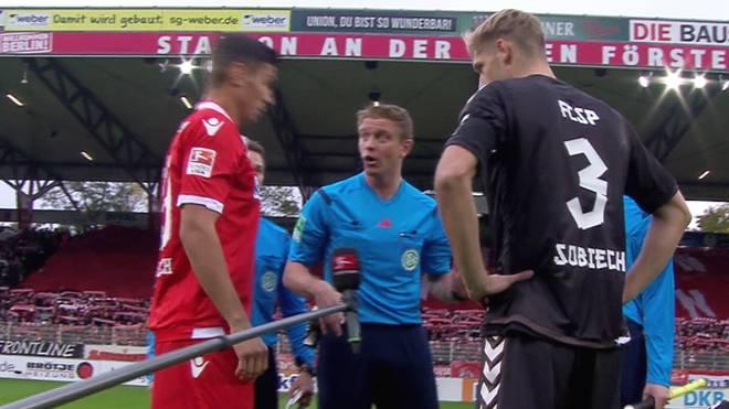 Schiedsrichter Robert Schröder trifft Spieler mit Münze