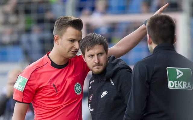 Aue-Trainer Hannes Drews (M.) musste nach einem Flaschenwurf auf die Tribüne