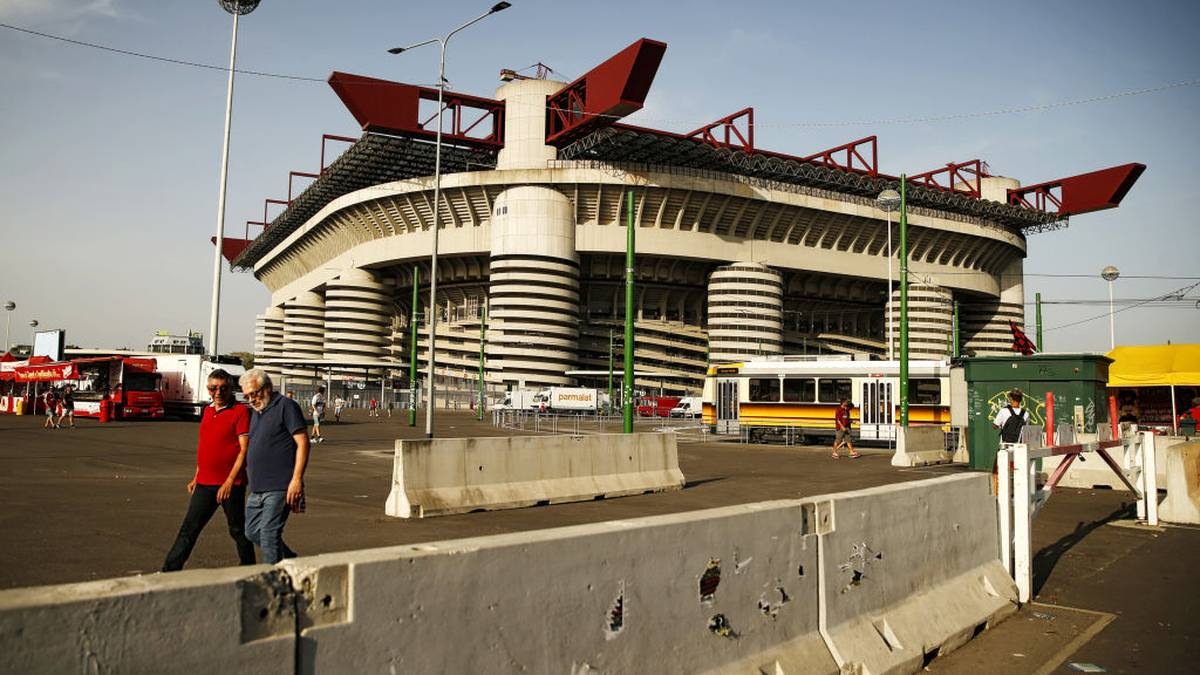 People walk past concrete barriers placed at the entrance of the Giuseppe Meazza Stadium in Milan on August 27, 2017. / AFP PHOTO / Marco BERTORELLO        (Photo credit should read MARCO BERTORELLO/AFP/Getty Images)
