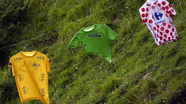 Die drei Trikots (gelb, grün, gepunktet, v.l.) hängen an einer Leine