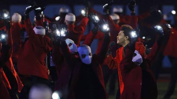 The Weeknd wird von den Masken-Menschen umkreist beim Super Bowl