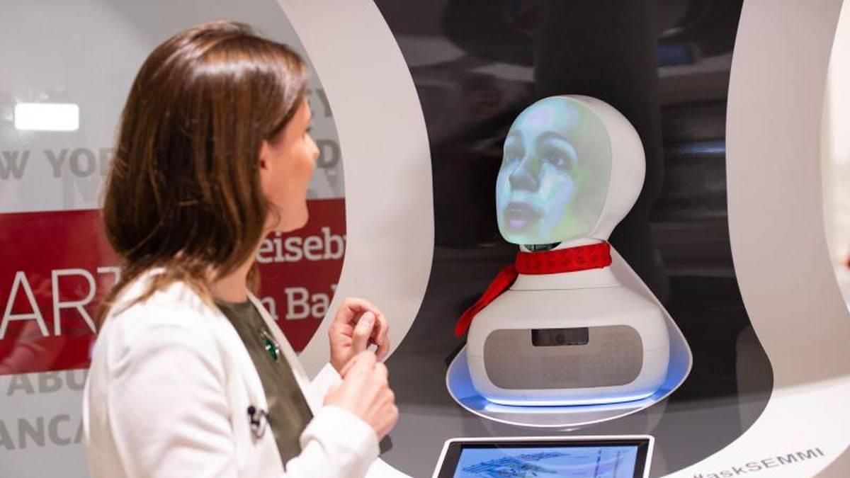 Eine Frau spricht im Reisenzetrum des Hauptbahnhofs mit «Semmi», einem Roboter vom Kundenservice der Deutsche Bahn, der auf Basis Künstlicher Intelligenz (KI) funktioniert.