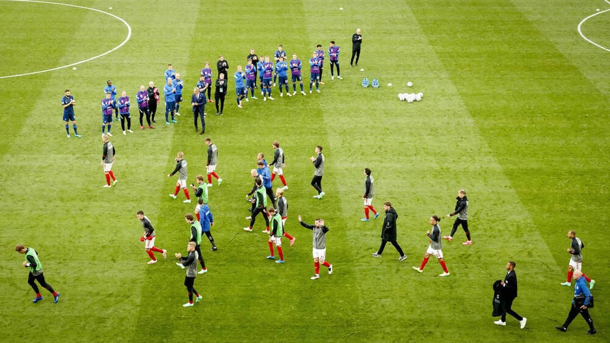 Die dänischen und finnischen Spieler kehren nach rund eineinhalbstündiger Unterbrechung auf den Platz zurück