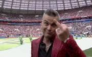 Typisch Robbie: der ausgefallene Rockstar zeigt der Kamera bei der Eröffnungsfeier seinen Mittelfinger. Ein Grund für seine Aktion war nicht ersichtlich