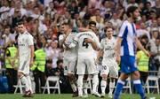 Marco Asensio (M.) wird von seinen Teamkollegen bei Real Madrid geherzt