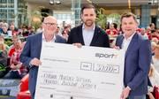 Christoph Metzelder (M.) erhält den Scheck für seine Stiftung von Siegfried Steltenkötter, Vertriebsleitung SCHÖNER WOHNEN-FARBE (l.) und Volkswagen-Doppelpass-Moderator Thomas Helmer.