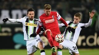 Mike Frantz vom SC Freiburg gegen zwei Gladbacher
