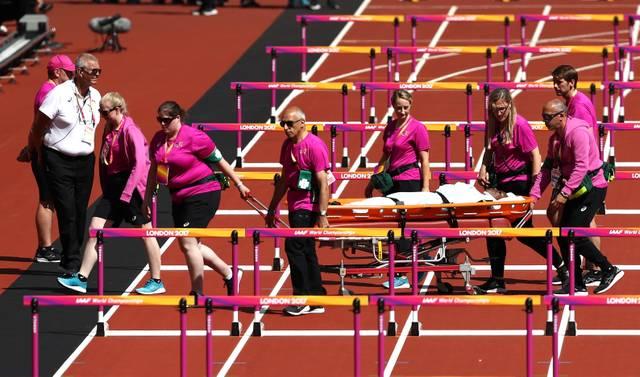 Deborah John aus Trinidad und Tobago wird bei der Leichtathletik-WM von Helfern von der Bahn getragen