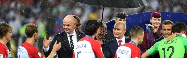 FRusslands Präsident Wladimir Putin bleibt bei der Siegerehrung als einziger trockenrance v Croatia - 2018 FIFA World Cup Russia Final