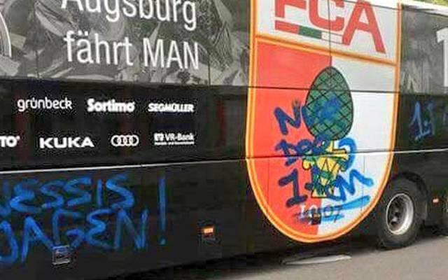 Augsburgs Stadionsprecher Rolf Störmann zeigt den Mannschaftsbus nach dem Vorfall bei Twitter