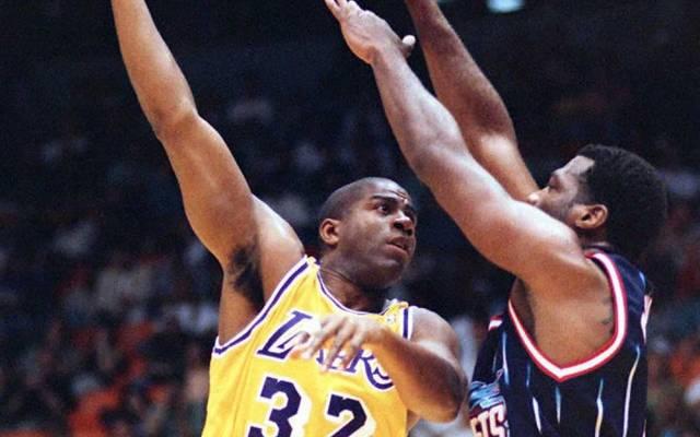 Los Angeles Lakers Earvin 'Magic' Johnson (L) shoo