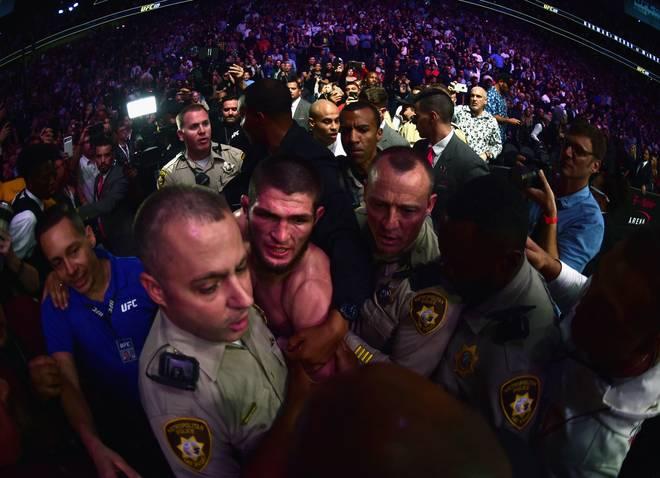 UFC 229: Khabib Nurmagomedov (M.) wird von Sicherheitskräften aus der Arena in Las Vegas geführt, nachdem sich dieser in die Menge geworfen hat