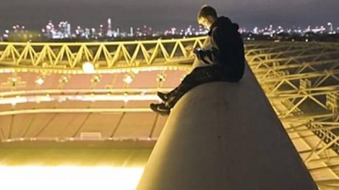 Der junge Kletterer sitzt auf dem Dach des Emirates Stadium